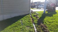 Underground Downspout Drainage is better for your yard and foundation to get water away with PVC Pipe and covered with SOD after trenching with Jolly Lawncare and Landscaping in Columbia MO
